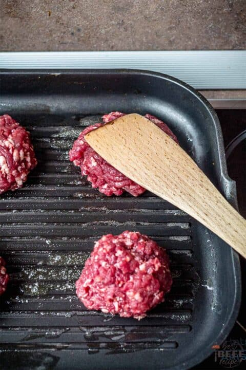 Smashing burgers on griddle pan with a spatula