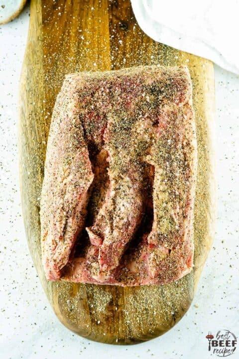 Seasoned prime rib on a cutting board