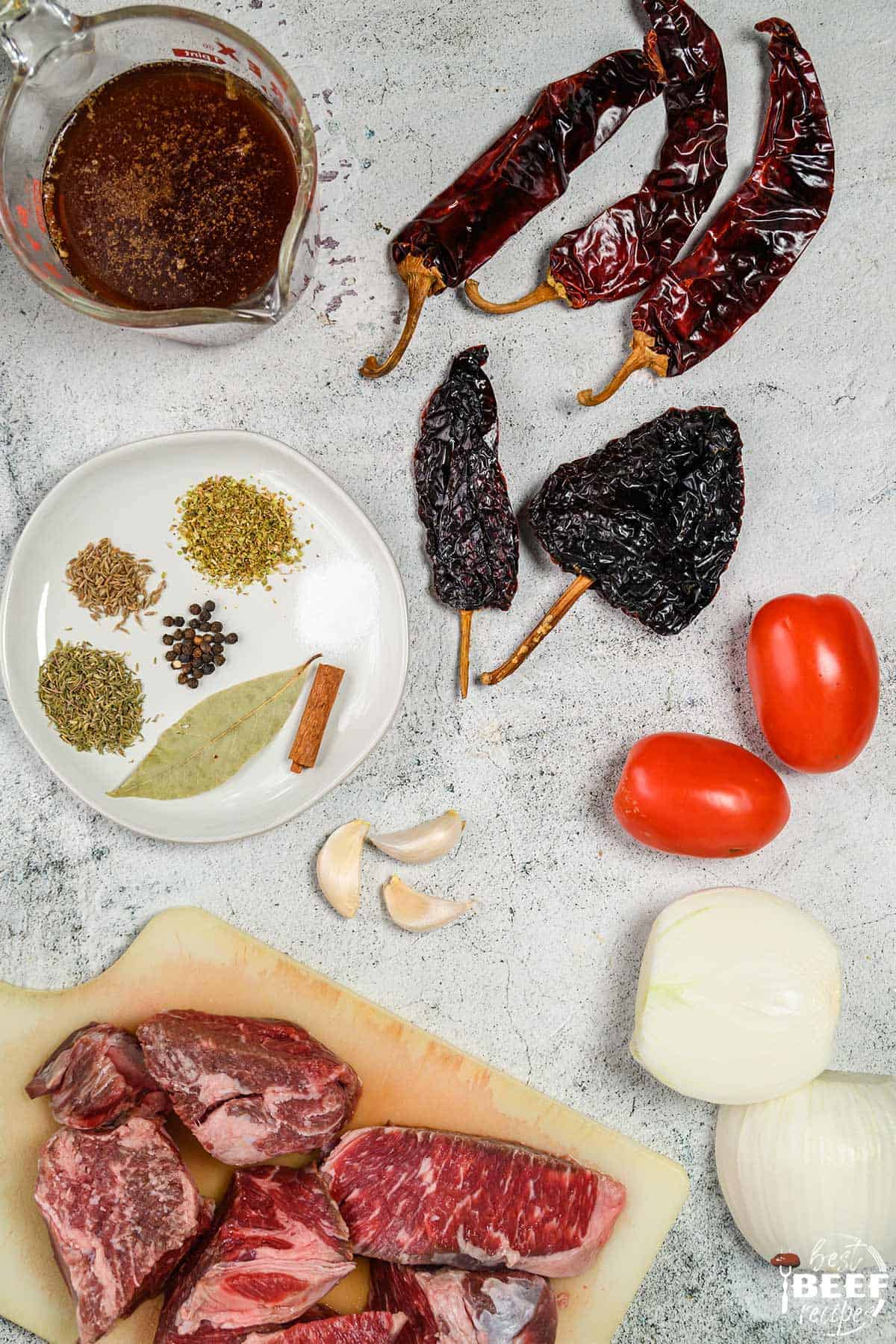 Ingredients to make beef birria stew on a white surface