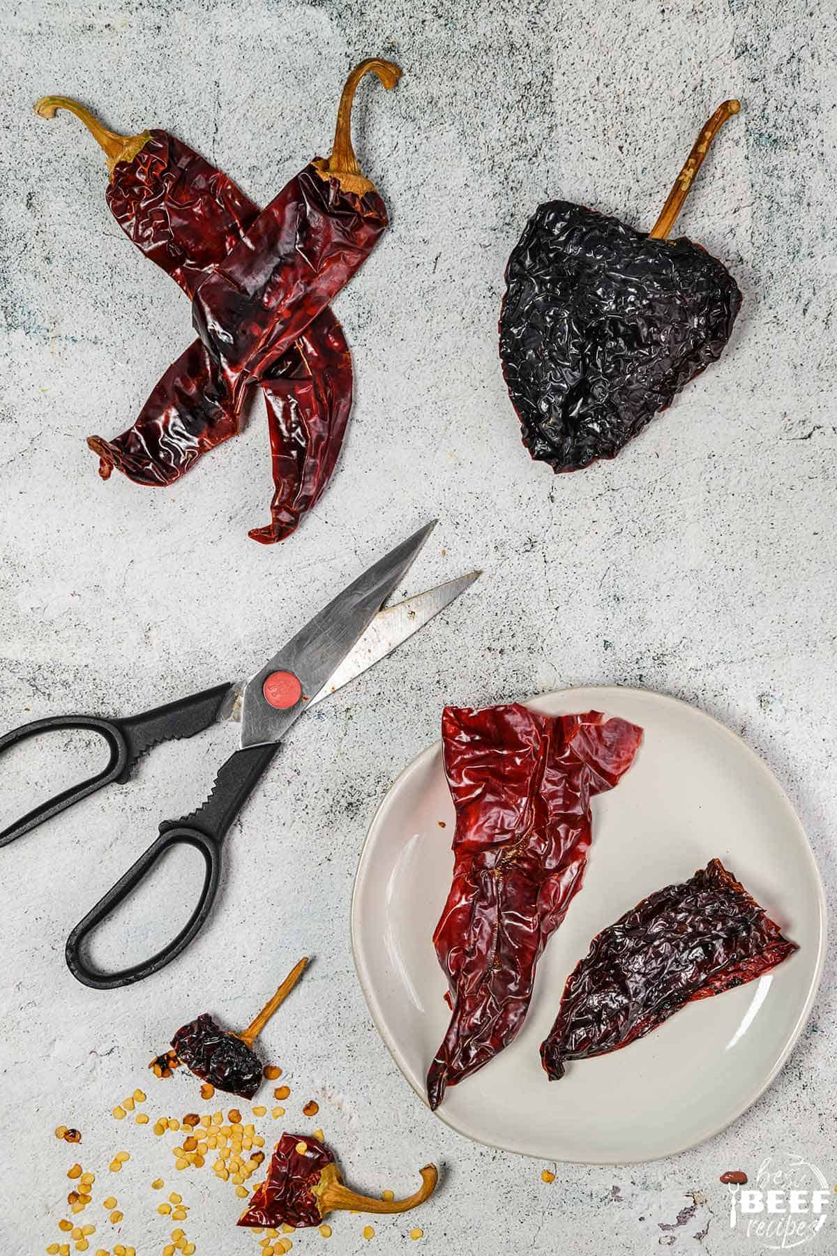 Guajillo and ancho chiles on a surface with scissors and a bowl