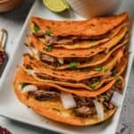 Beef birria tacos on a white platter