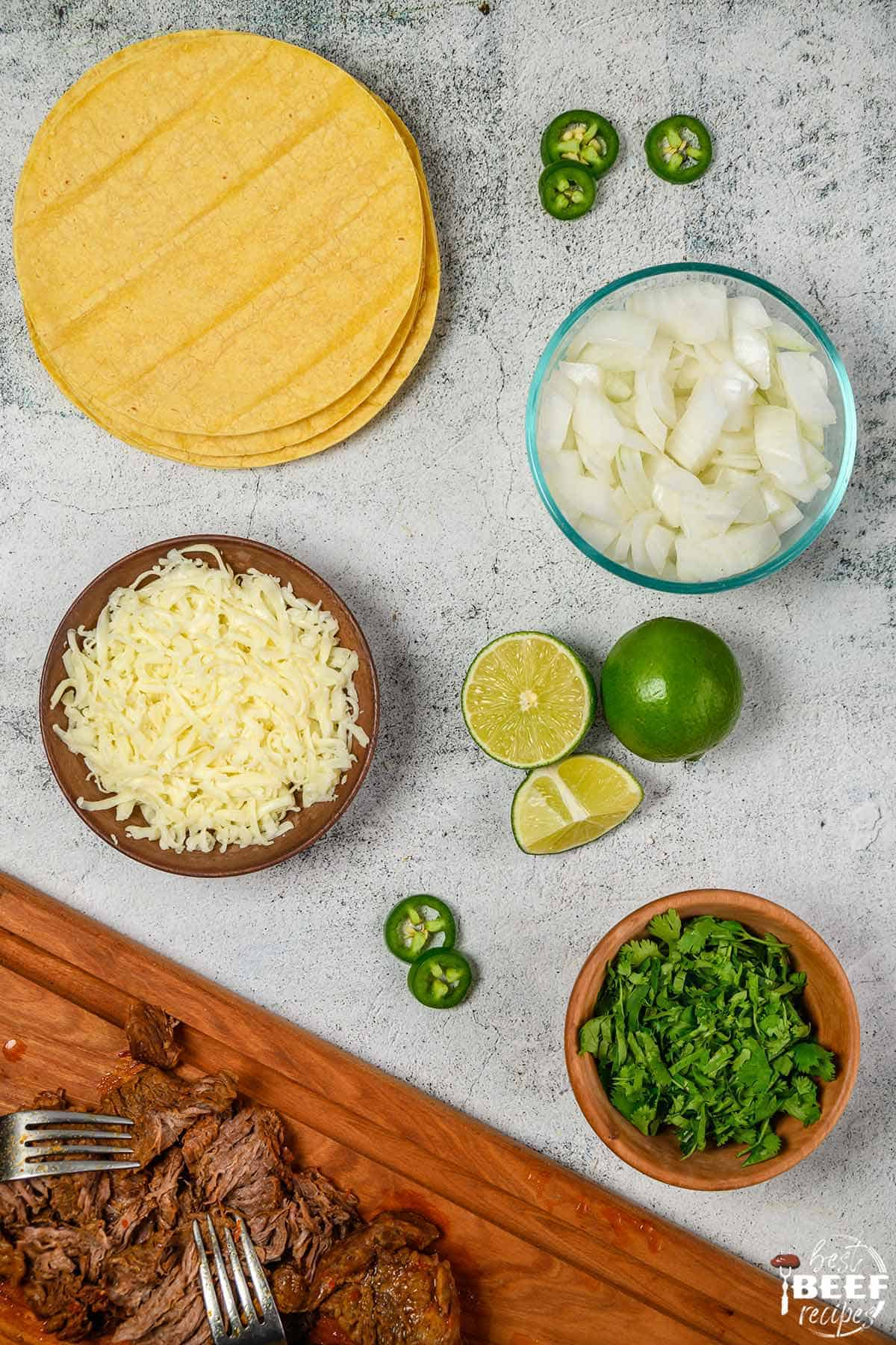 Beef birria tacos ingredients on a white surface