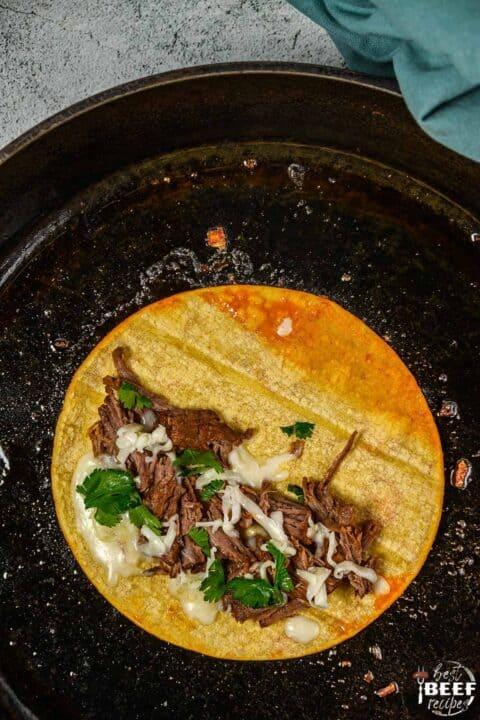 Beef birria tacos in a skillet