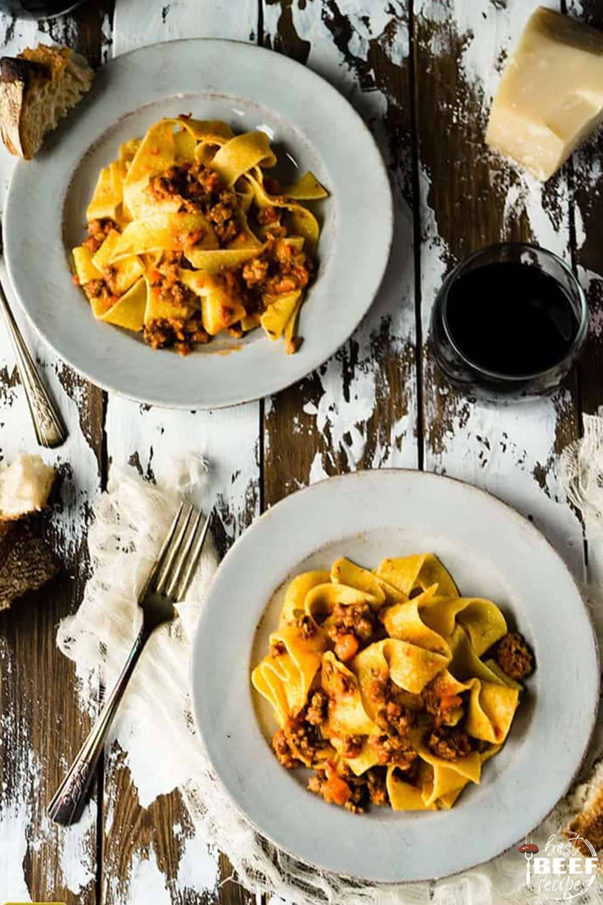 Two plates of beef bolognese with pappardelle pasta