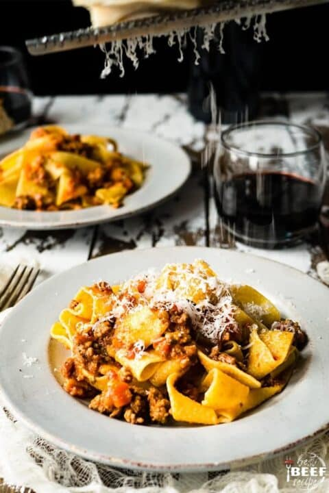 Grating cheese on top of pappardelle pasta with beef bolognese sauce on a plate