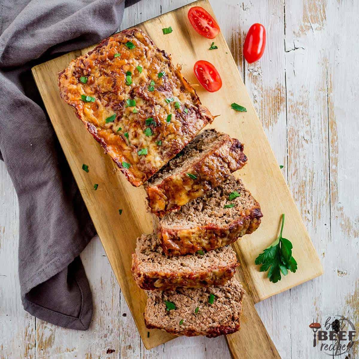 Keto meatloaf on a wooden serving board sliced