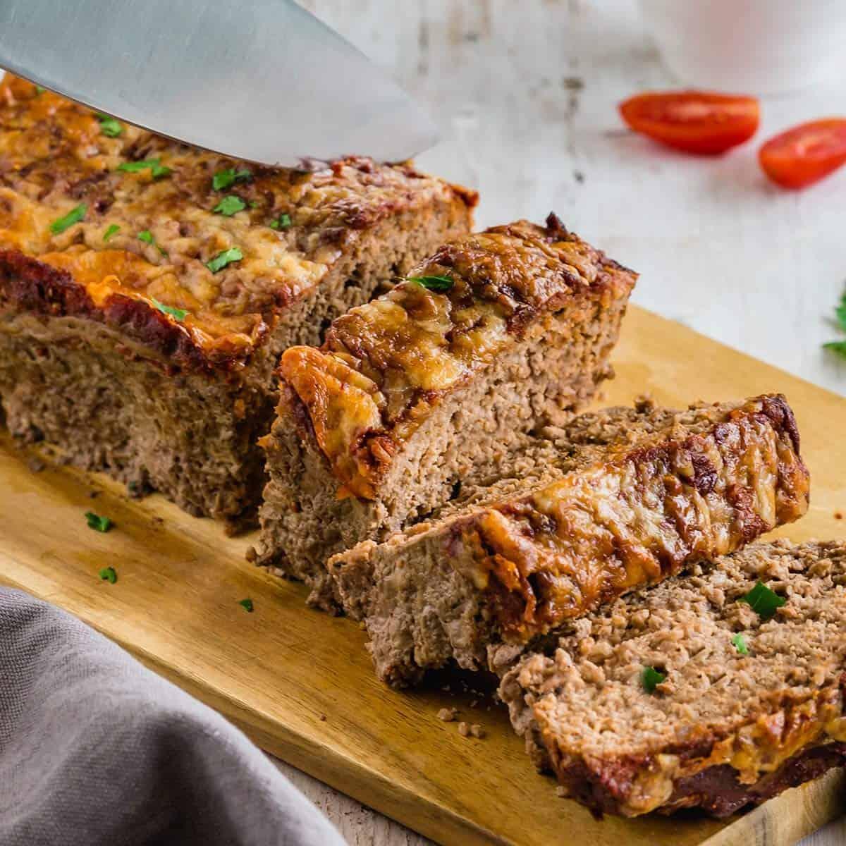 Full keto meatloaf seasoned with homemade meatloaf seasoning on serving board