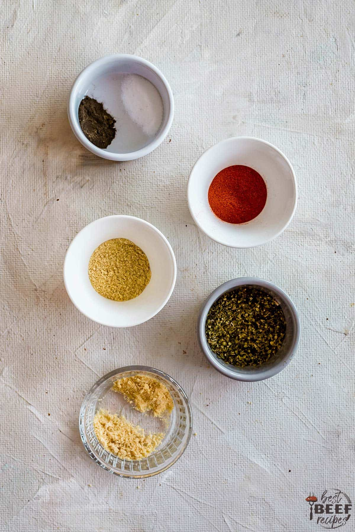 Salt and pepper, paprika, dried mustard, dried basil, garlic and onion powder in bowls
