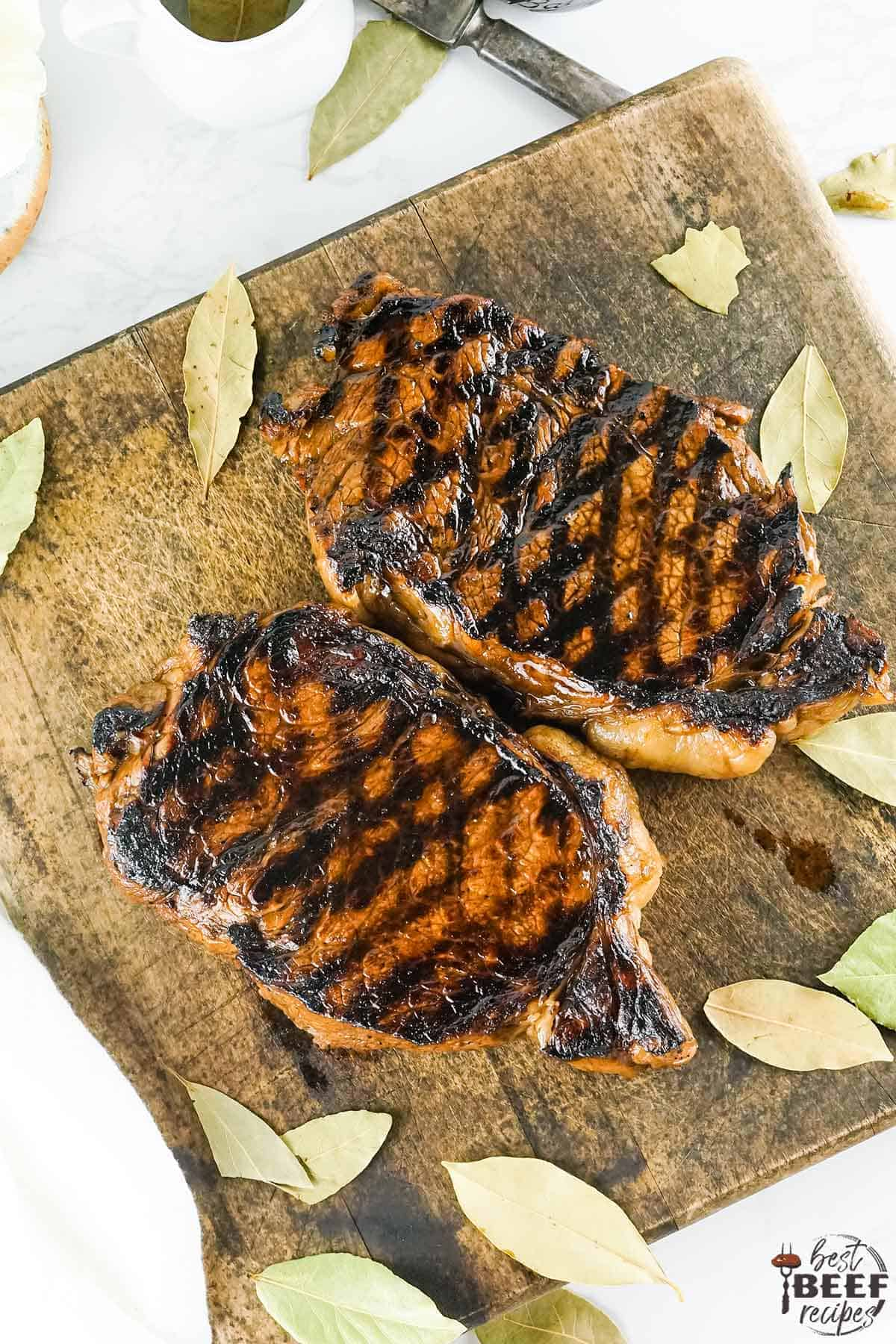 Grilled New york strip steaks on a cutting board up close