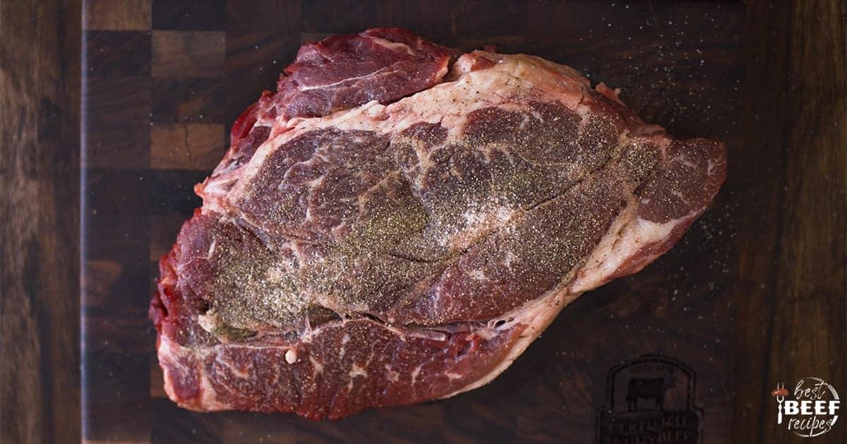Seasoned beef chuck roast on a cutting board