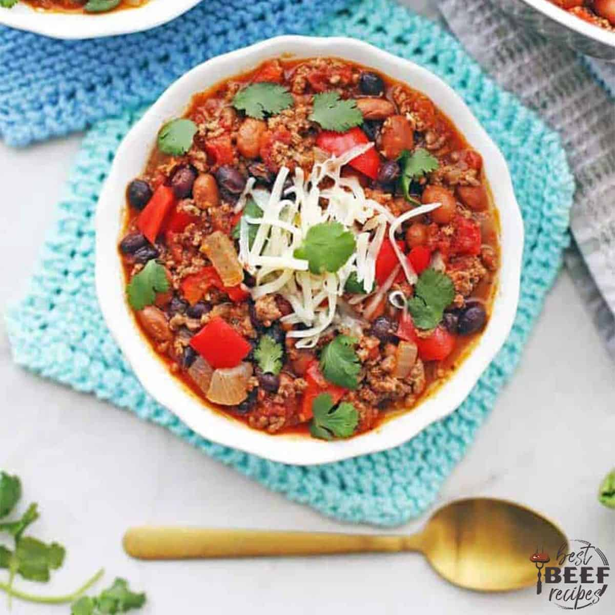 Ground beef chili in a white bowl with a spoon