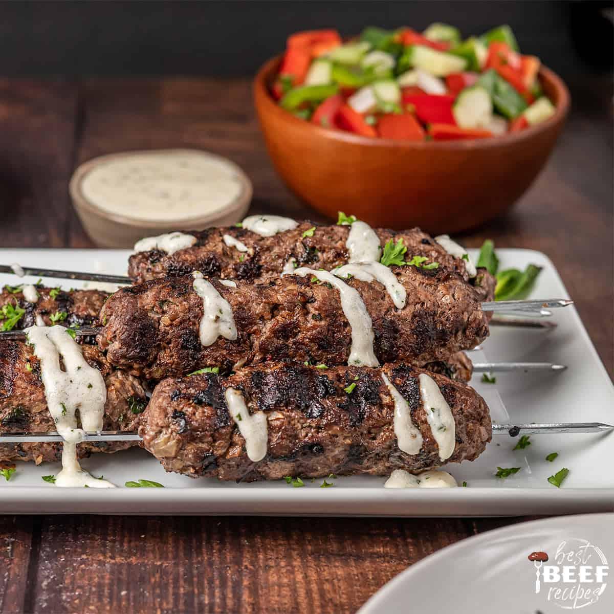 Kofta kebabs on a white platter with garlic sauce