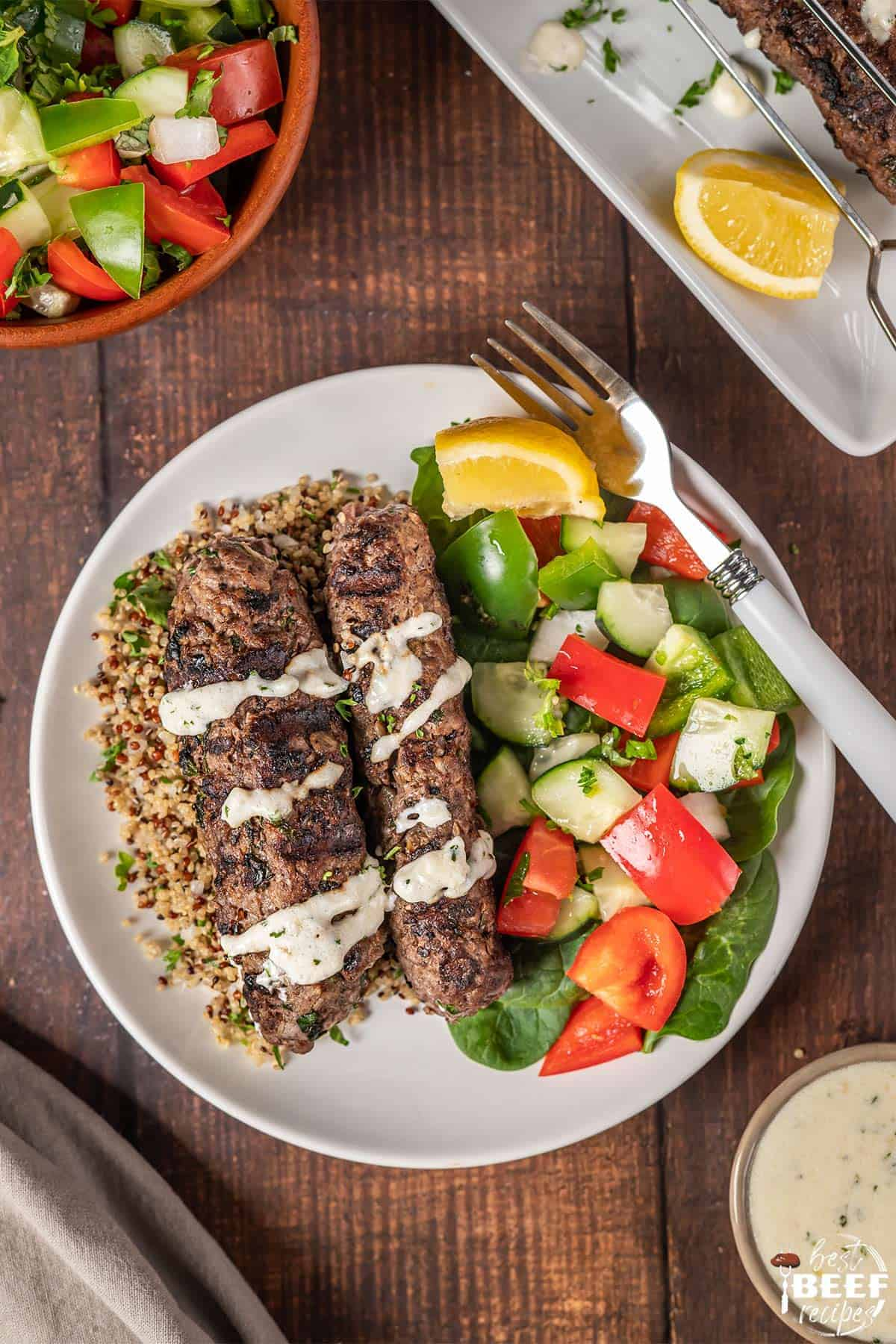 Kofta kebabs on a white plate with vegetables on the side