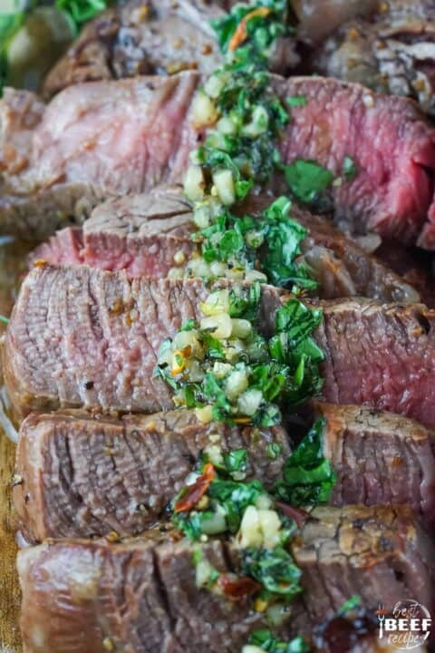 Chimichurri sauce over slices of steak