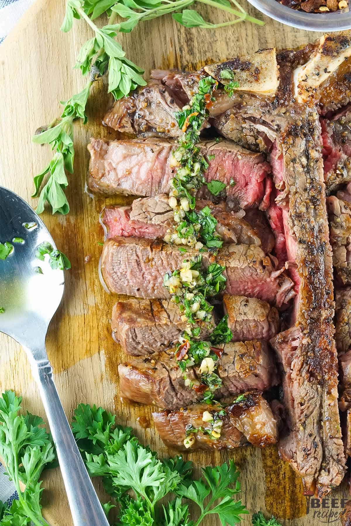 Slices of porterhouse steak with chimichurri sauce