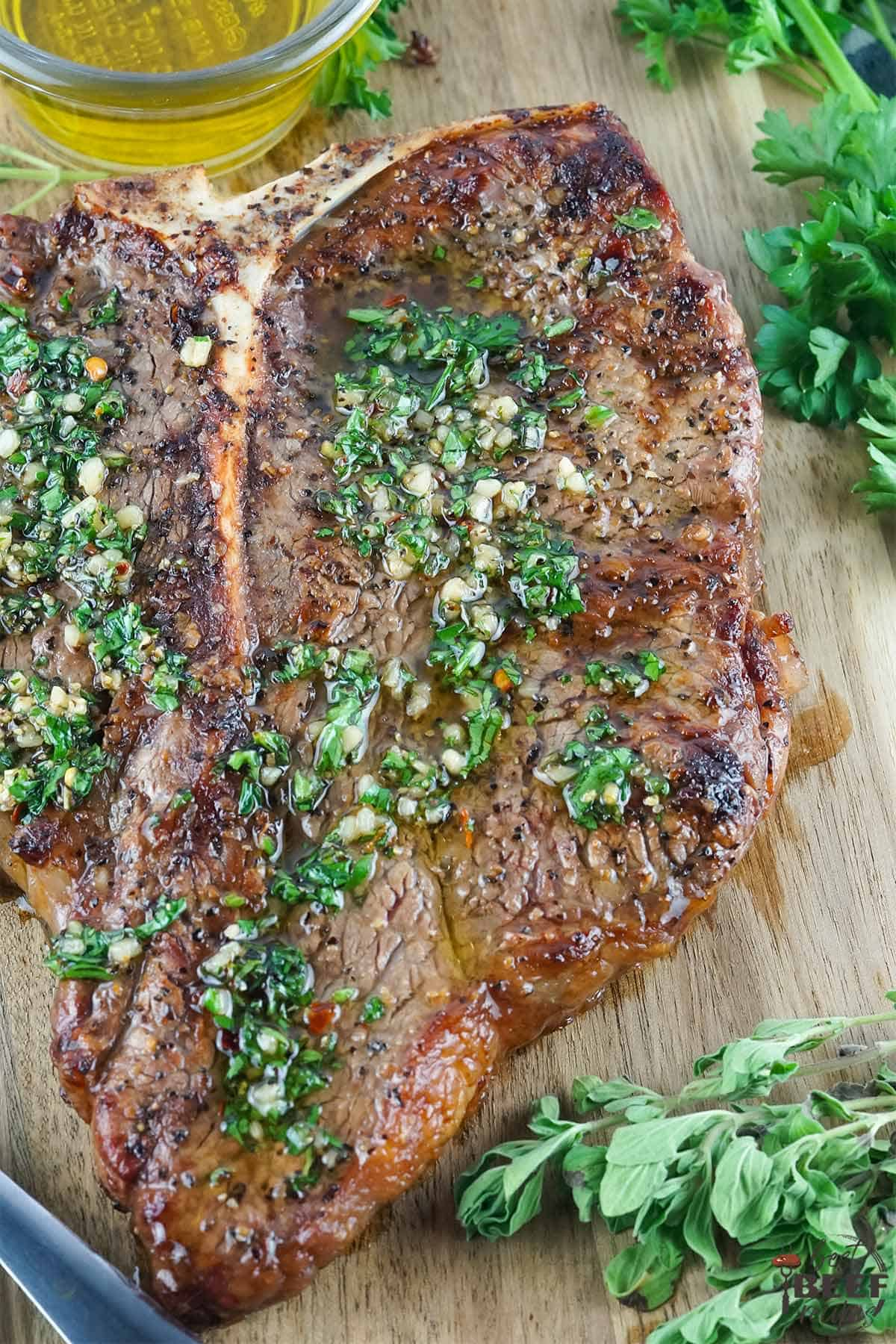 Whole grilled porterhouse steak with chimichurri sauce on a cutting board