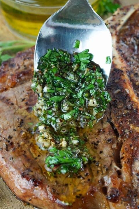 Spooning chimichurri sauce over porterhouse steak