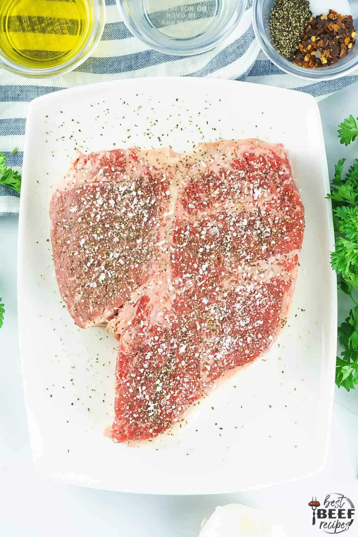 seasoned porterhouse steak on a cutting board