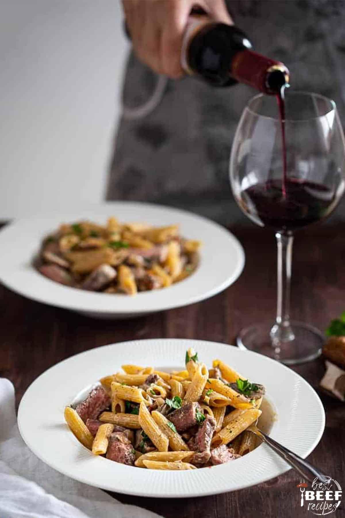pouring wine next to two plates of leftover prime rib pasta