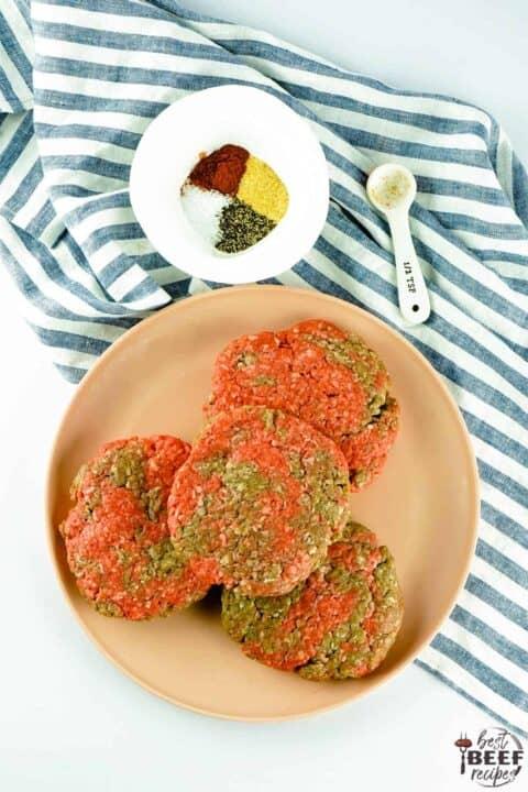 seasoned burger patties on a plate