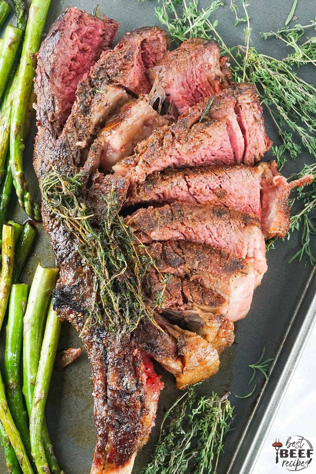 Sliced tomahawk steak overhead shot on a tray with asparagus and thyme