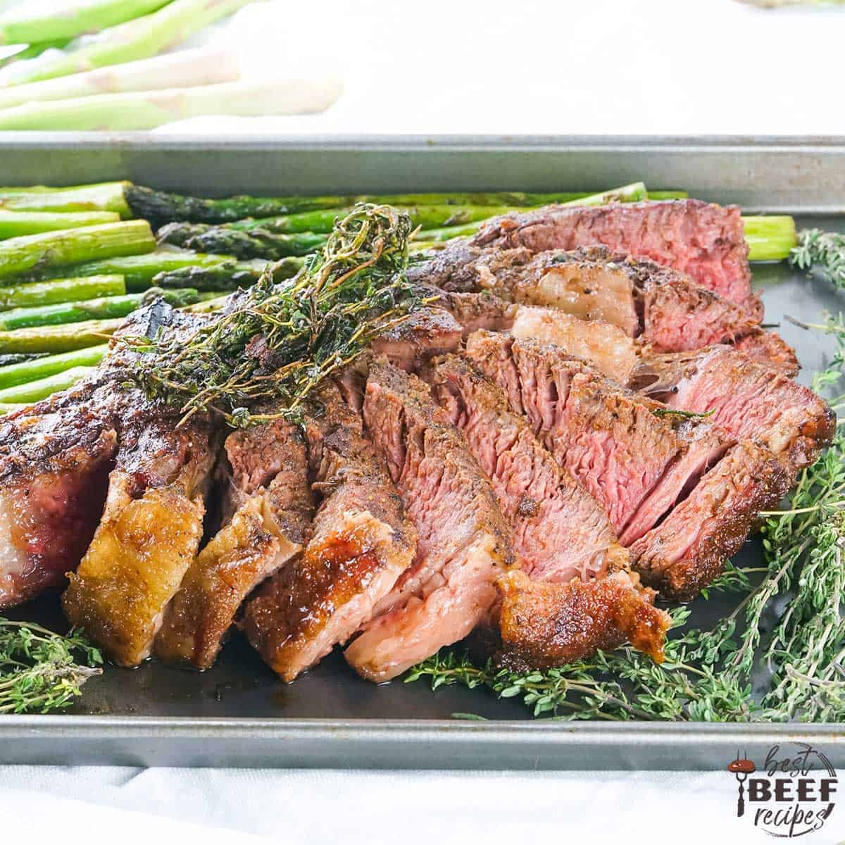 Sliced tomahawk steak on a tray with asparagus and thyme