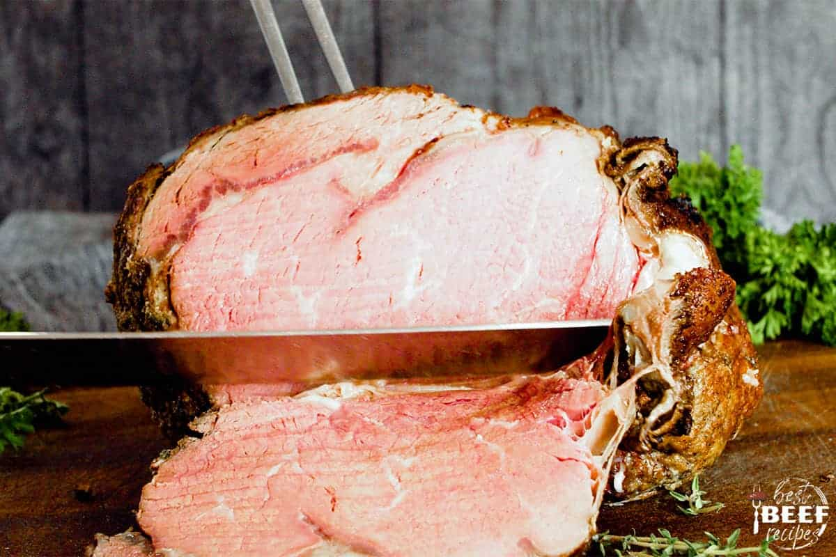 Slicing prime rib on a cutting board with a sharp knife