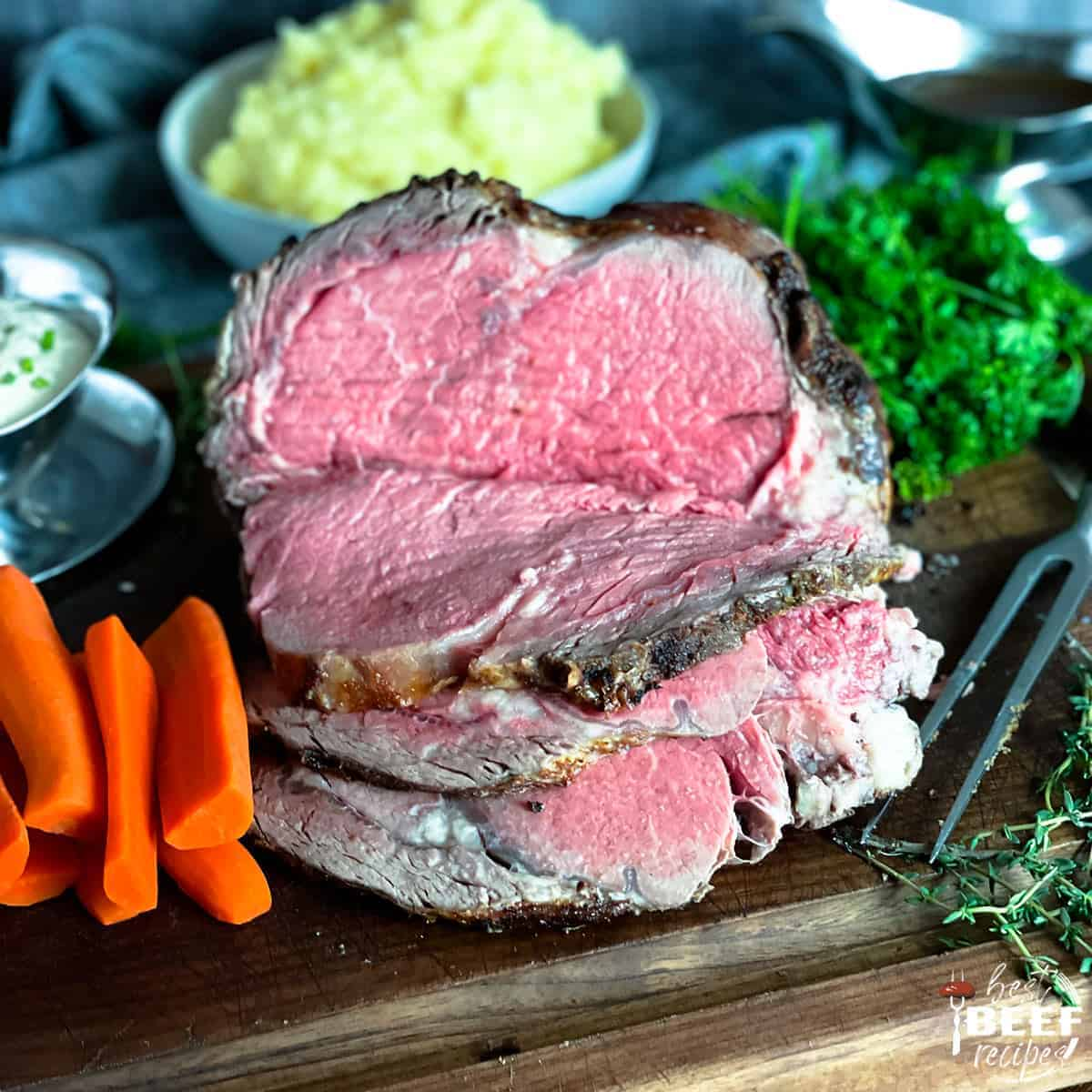 Sous vide prime rib sliced on a cutting board next to carrots and greens