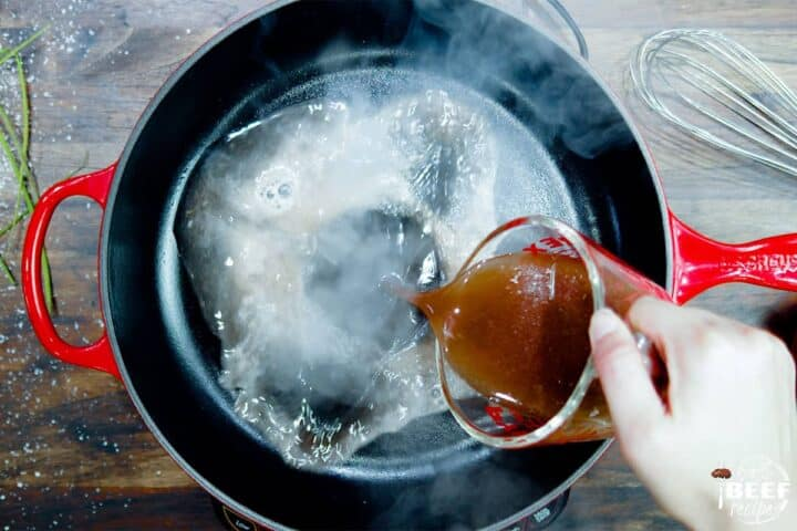 Adding cooking liquid and beef broth to a pan