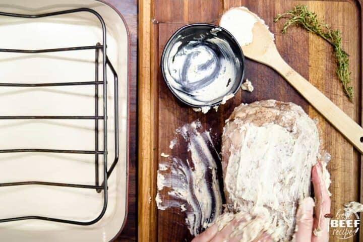Slathering garlic butter over prime rib